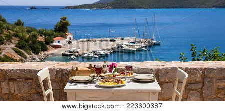 A table served for two with chicken souvlaki french fries, greek salad, snacks and drinks on the summer terrace of the hotel room by the seascape, beautiful summer greek holidays concept. Daylight.