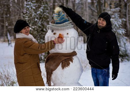 Mother and adult son sculpt a big real snowman, Happy family in winter park