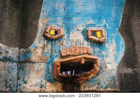 Vienna, Austria - 01 October, 2017: The funny detail of facade of Hundertwasser house with multicolored walls. Water drain disguised as a face. Vienna, Austria