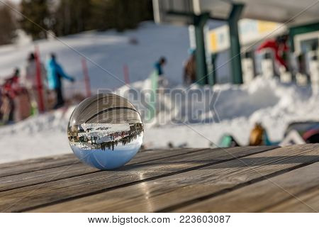 Glass ball on a wooden table in the Dolomites. A view across the globe around us. Sunny day in Dolomites. Alpe di Lusia. Dolomites. Italy
