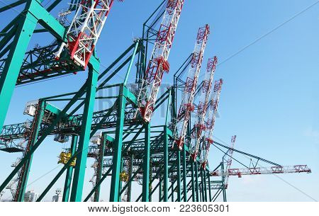 Huge container handling gantry cranes at a container terminal. Blue sky background