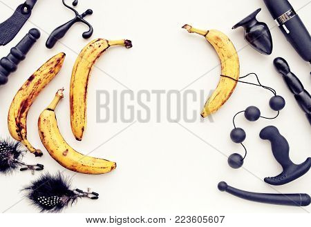 A variety of sex toys (anal balls, dildo, vibrator, prostate massager, butt plug) and bananas on a light background. There is an empty space for the text. Image is suitable for sex shop advertising