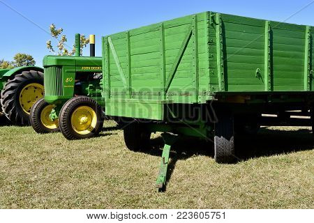 DALTON, MINNESOTA, September 9, 2107:  A Power Steering 80 John Deere tractor is parked partially behind a homemade green wagon box resting on a four wheeled trailer at the threshing show occurring each second weekend of September.