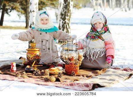 Two little girls in fur coats and shawls in Russian style on his head against the background of a samovar. The celebration of Shrovetide in Russia.
