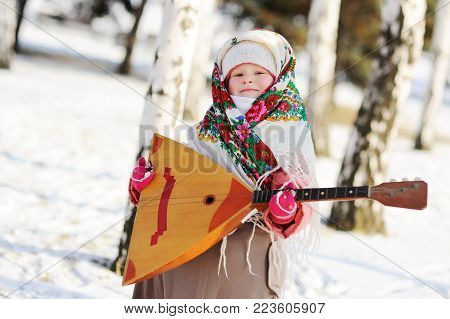child girl in a fur coat and a scarf in Russian with a balalaika in the hands on the background of the forest and snow
