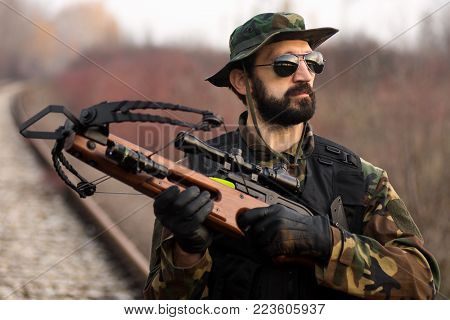 Portrait of man in military uniform with crossbow weapon outdoors.