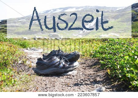 German Text Auszeit Means Downtime. Trekking Shoes On Hiking Path In Norway. Mountains In The Background