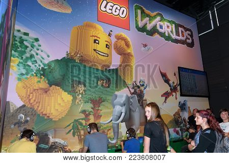Cologne, Germany - August 24, 2017: Trade fair visitors playing Lego Worlds at the booth of the company Lego at Gamescom 2017. Gamescom is a trade fair for video games held annually in Cologne.