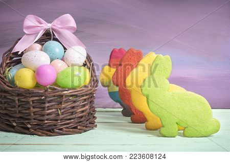 Bunny shaped cookies and Easter eggs - Easter card with a wicker basket full of painted eggs, with a pink ribbon bow and multicolor bunny shaped cookies, on a green table and purple wall.