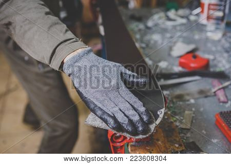 A man in work clothes repairman in a workshop ski service repairing the sliding surface of skis. In the hands of a tool, Final polishing. Theme ski repair and maintenance of equipment.