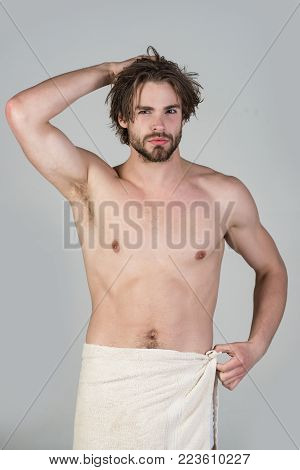 Man in bathroom with muscular body on grey background. Man with wet hair hold towel after shower. Hygiene, sexy guy wash, spa, relax. Morning washing, wake up, everyday life. Refreshment, healthcare.