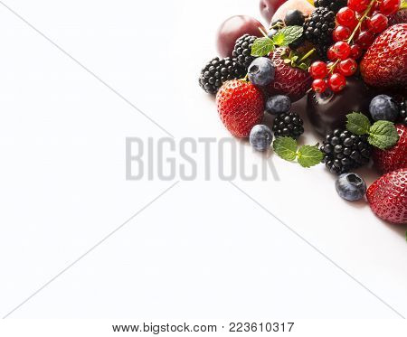 Mix berries on a white background. Ripe blueberries, blackberries, red currants, strawberries, black currant and plums. Various fresh summer berries on white background. Berries and fruits with copy space for text. Background berries. Top view.