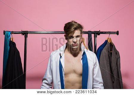 Macho with sexy torso in open shirt, necktie in wardrobe on pink background. Business fashion, style concept. Clothing, dressing, closet. Shopping, sale, purchase