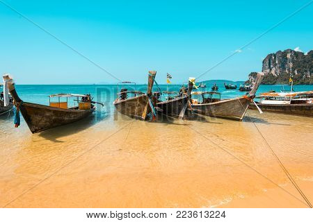 Longtail boats in Railay beach on the Andaman sea water. Krabi peninsula in Thailand. Teal and orange mood