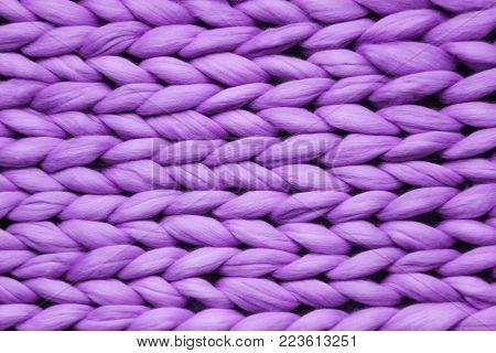 Texture of purple big knit blanket. Large knitting. Plaid merino wool. Top view