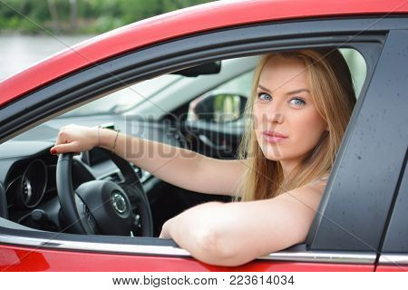 Young, attractive blonde girl in new red car holds the wheel and looks out of the car window