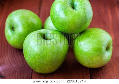Sour green apples of Simirenko on a wooden table in a rustic style