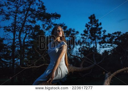 Young blonde in night forest looking around anxiously.