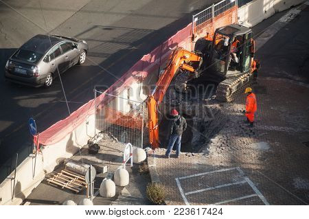 Genova, Italy - January 18, 2018: Road works are in progress, workers dig hole in asphalt with orange excavator