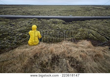 Person In A Yellow Jacket Sits On The Cliff Covered With Faded Grass On The Background Of The Roadwa
