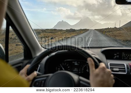 Person Is Driving A Car On The Country Roadway Between Brown Fields On The Background Of The Mountai