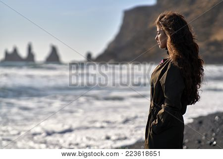 Gorgeous Girl Stands On The Black Sand Beach On The Background Of The Rocky Cliffs And The Stormy Se