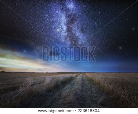 Fine art landscape with starry sky over stubble field. Beautiful dreamy landscape.