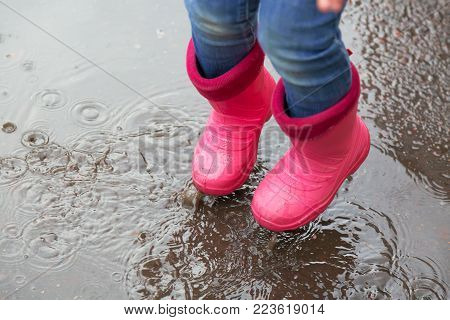 The girl in pink boots jumping in puddles after rain outdoors. Autumn concept