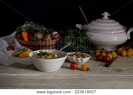 Fresh, mushroom soup-puree in a bowl, tureen, crouton and vegetables in a wicker basket on a wooden table close-up