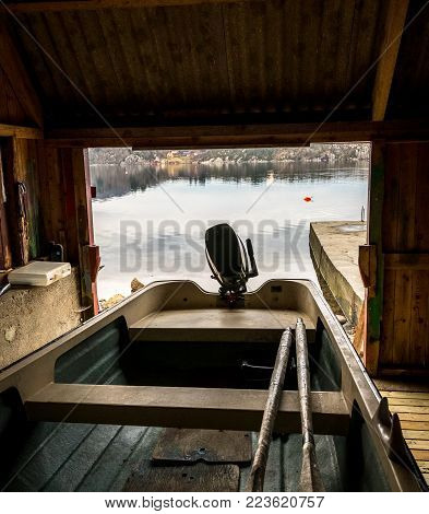 Boat house with a small boat, seen from the inside, looking out at the ocean. Norway.
