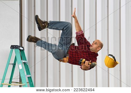 Worker falling from ladder while holding drill