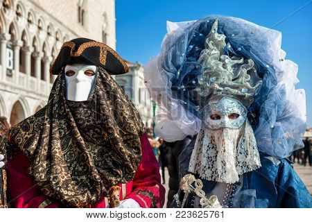 VENICE, ITALY - FEBRUARY 18, 2017: Couple of unidentified participants wear colorful costumes and masks during famous traditional Carnival taking place each year on february in Venice, Italy.