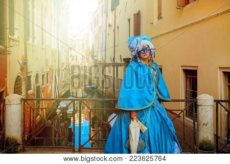 VENICE, ITALY - FEBRUARY 18, 2017: Woman wear vintage costume and mask posing on small bridge over narrow canal during famous traditional Carnival taking place each year on February in Venice, Italy.