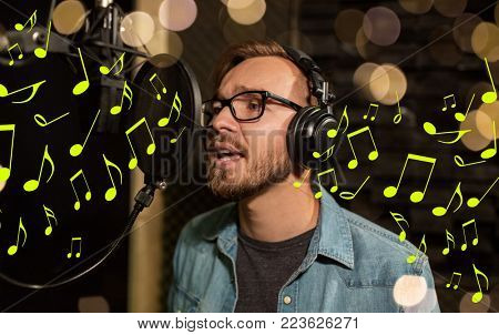 music, show business, people and voice concept - male singer with headphones and microphone singing song at sound recording studio over lights and notes