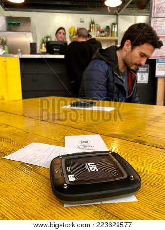 LONDON - JANUARY 23, 2018: Vibrating technology to alert a customer that their Pizza order is ready at Mercato Metropolitano in Elephant & Castle, South London, UK.