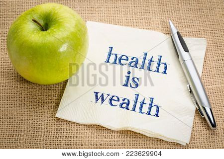 health is wealth inspirational reminder - handwriting on a napkin with a green apple