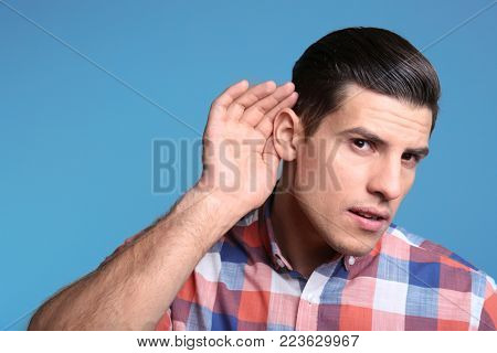Man with hearing problem on color background