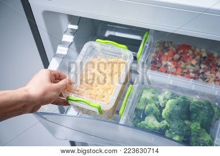 Woman taking container with frozen corn from refrigerator