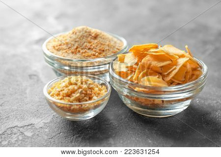 Dried garlic flakes, granules and powder in glass bowls on grey background