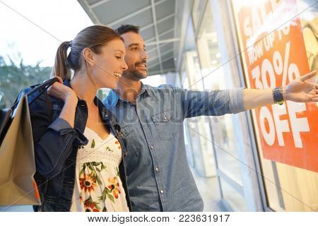 Couple in front of shop window during sales shopping