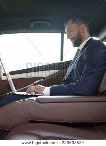 confident businessman sitting on the backseat of a prestigious car