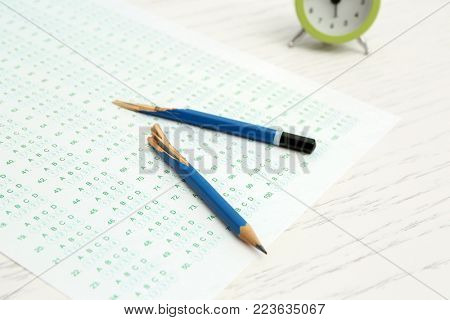 Broken pencil and test sheet on table, closeup. Preparation for exam