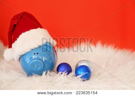 Piggy bank with Santa hat on faux fur