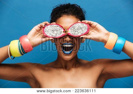 Portrait of young woman with bracelets on her arms having fun covering eyes with ripe pitahaya fruit cut in half isolated in studio over blue