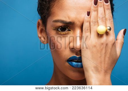 Colorful photo of scared or offended mixed-race woman with trendy makeup and accessories covering eye with hand over blue background