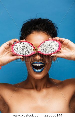 Vertical portrait of cheerful african american woman fooling around while covering eyes with exotic pitahaya fruit cut in half isolated in studio over blue