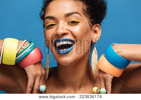 Closeup image of happy woman with colorful makeup laughing and showing beautiful adornment on her arms isolated over blue