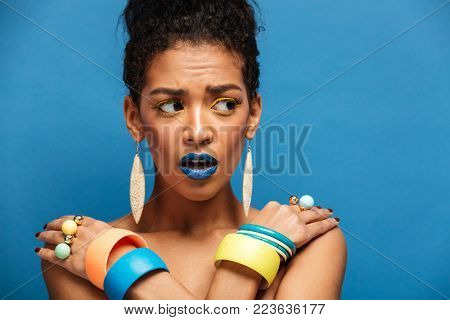 Photo of scared or agitated woman with colorful makeup and fashion accessories looking aside with crossed hands on shoulders over blue wall