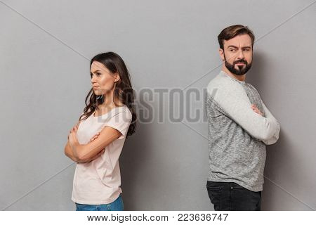 Portrait of a disappointed young couple having an argument over gray background