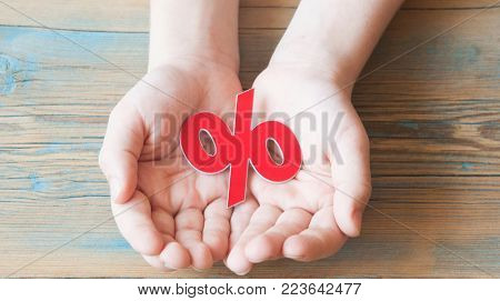 kid hands holding red percentage sign on wooden background.